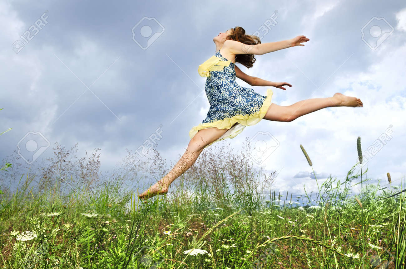 Young teenage girl jumping in summer meadow amid wildflowers Stock Photo - 5799023