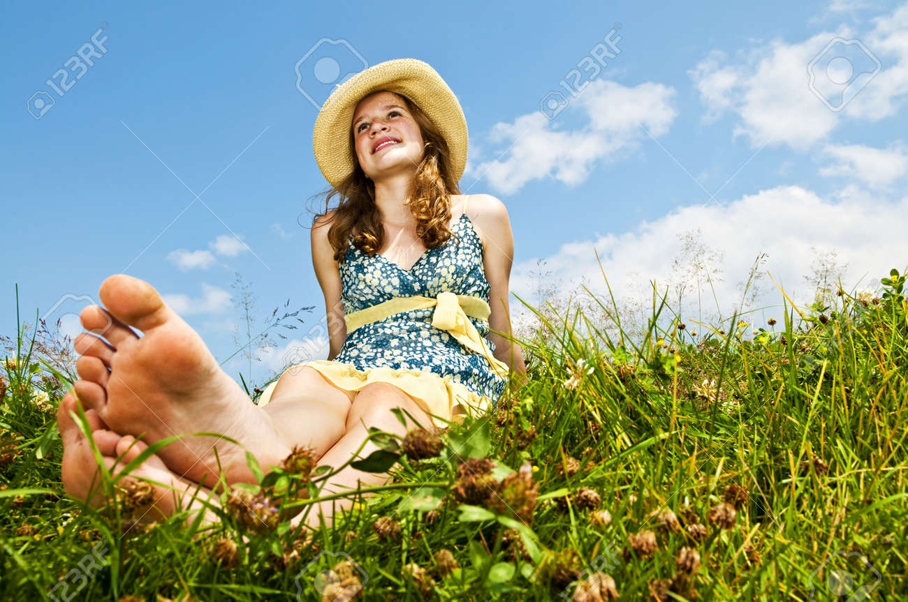 Young teenage girl sitting on summer meadow barefoot Stock Photo - 6219863