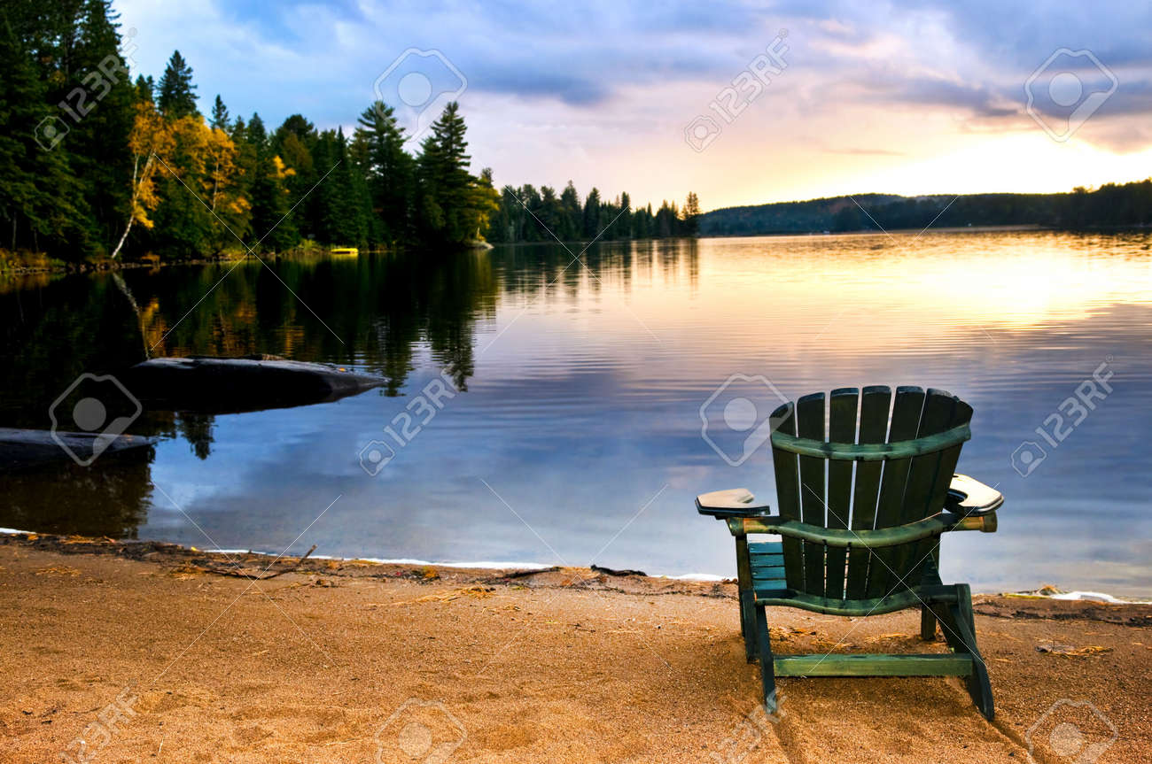 Beach sunset with chairs - Stock Photo Wooden Chair On Beach Of Relaxing Lake At Sunset