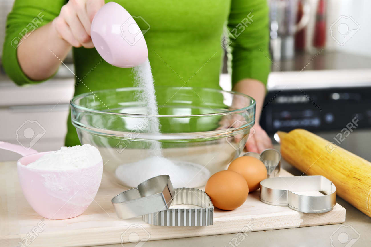 Pouring sugar into mixing bowl with ingredients for making cookies Stock Photo - 6431140