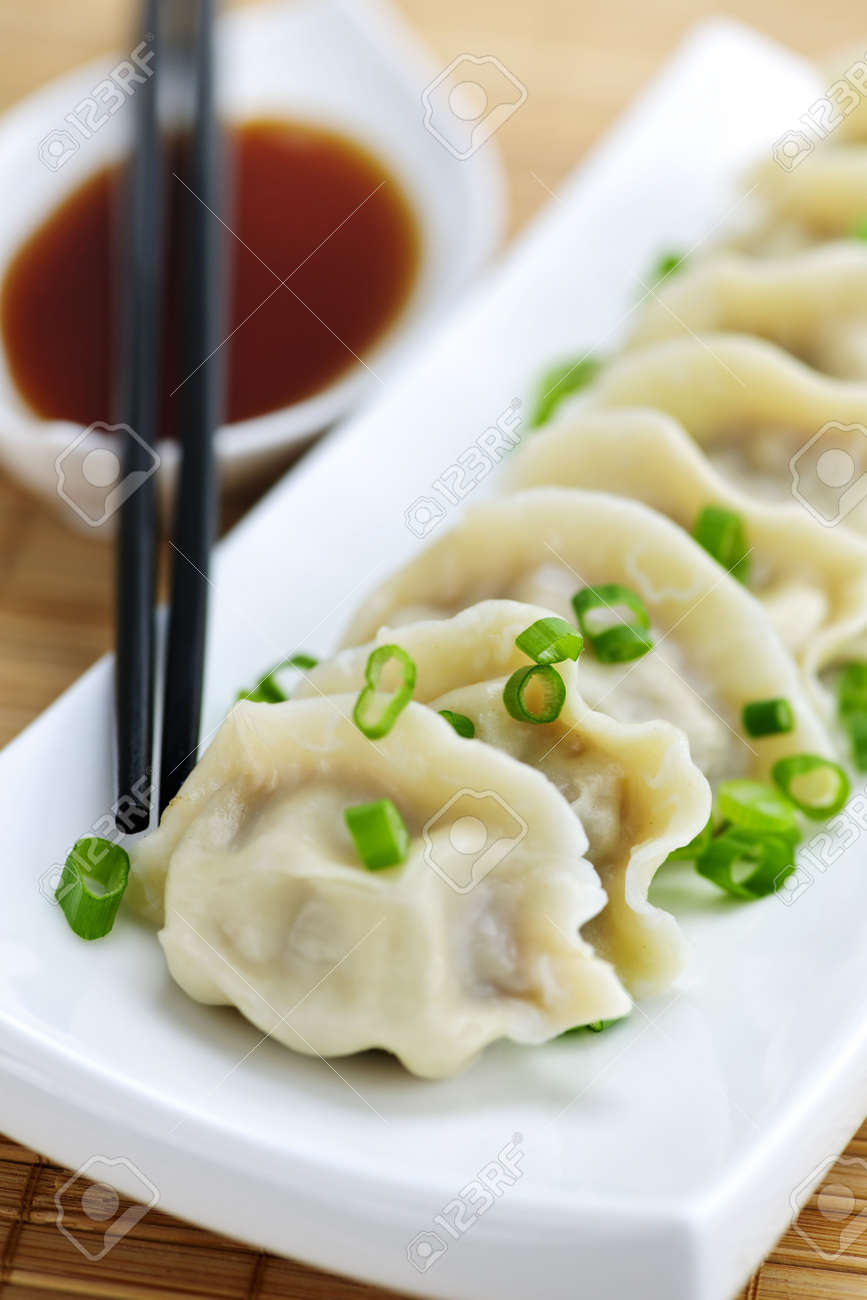 Plate of steamed dumplings with soy sauce and chopsticks Stock Photo - 6477446