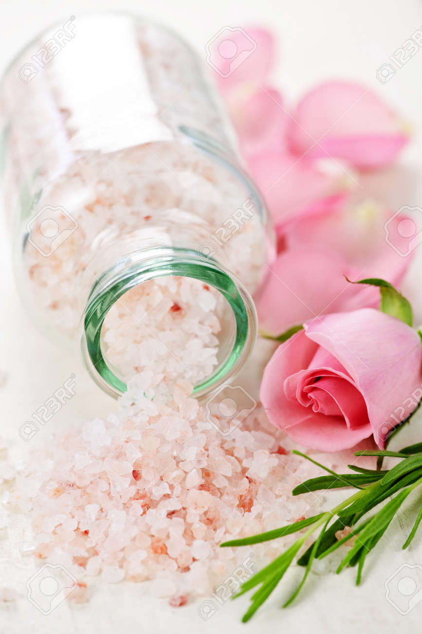 Pink bath salts in a glass jar with flowers and herbs - 6856905