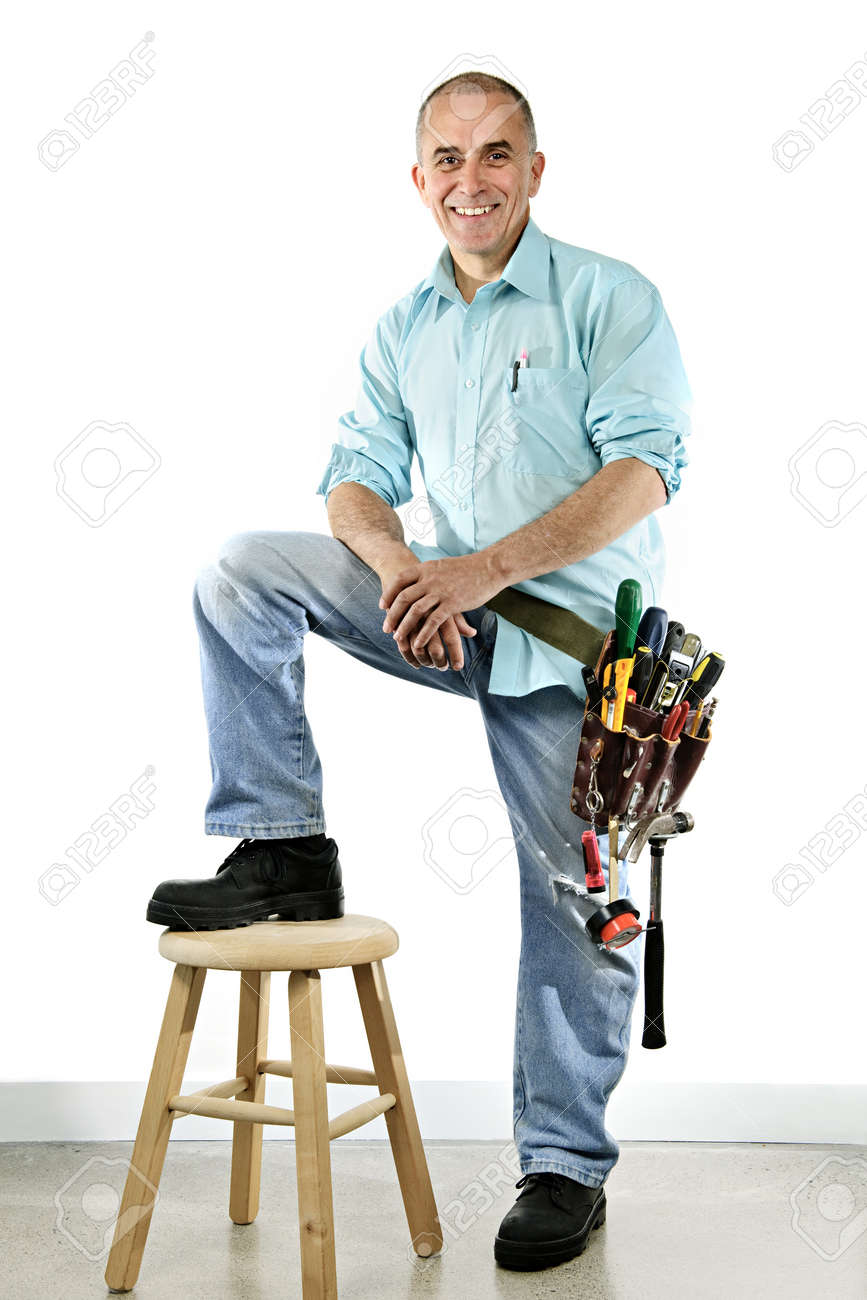 Portrait of smiling handyman with tool belt and stool Stock Photo - 7317231