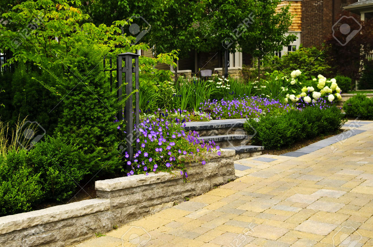 Natural stone landscaping in front of a house with lush green garden Stock Photo - 7305407