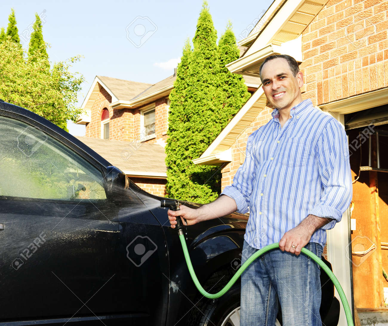 Man washing his car on the driveway Stock Photo - 7372968