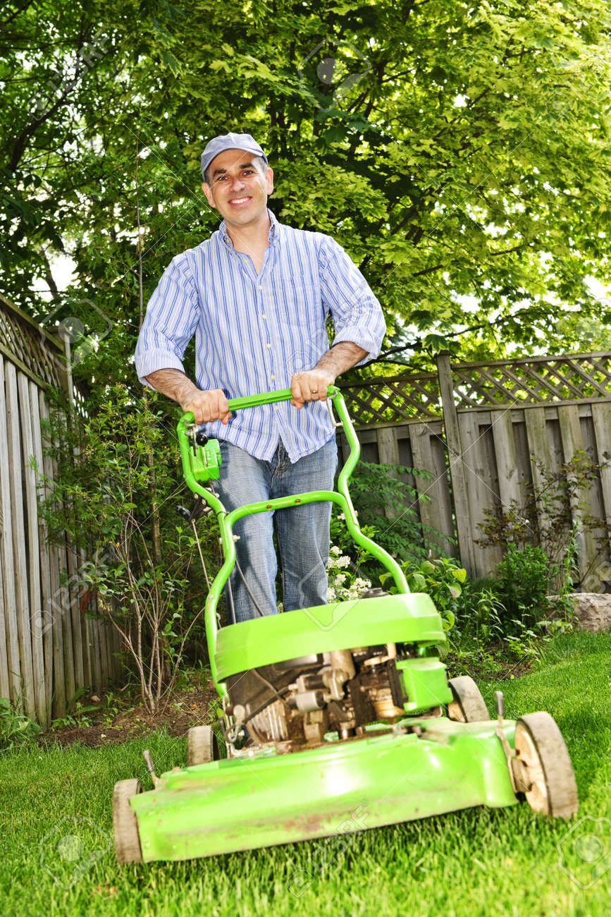 man with lawn mower in landscaped backyard stock photo picture