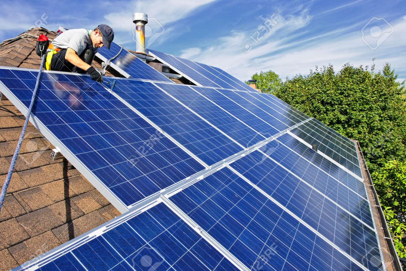 Man installing alternative energy photovoltaic solar panels on roof Stock Photo - 7881288