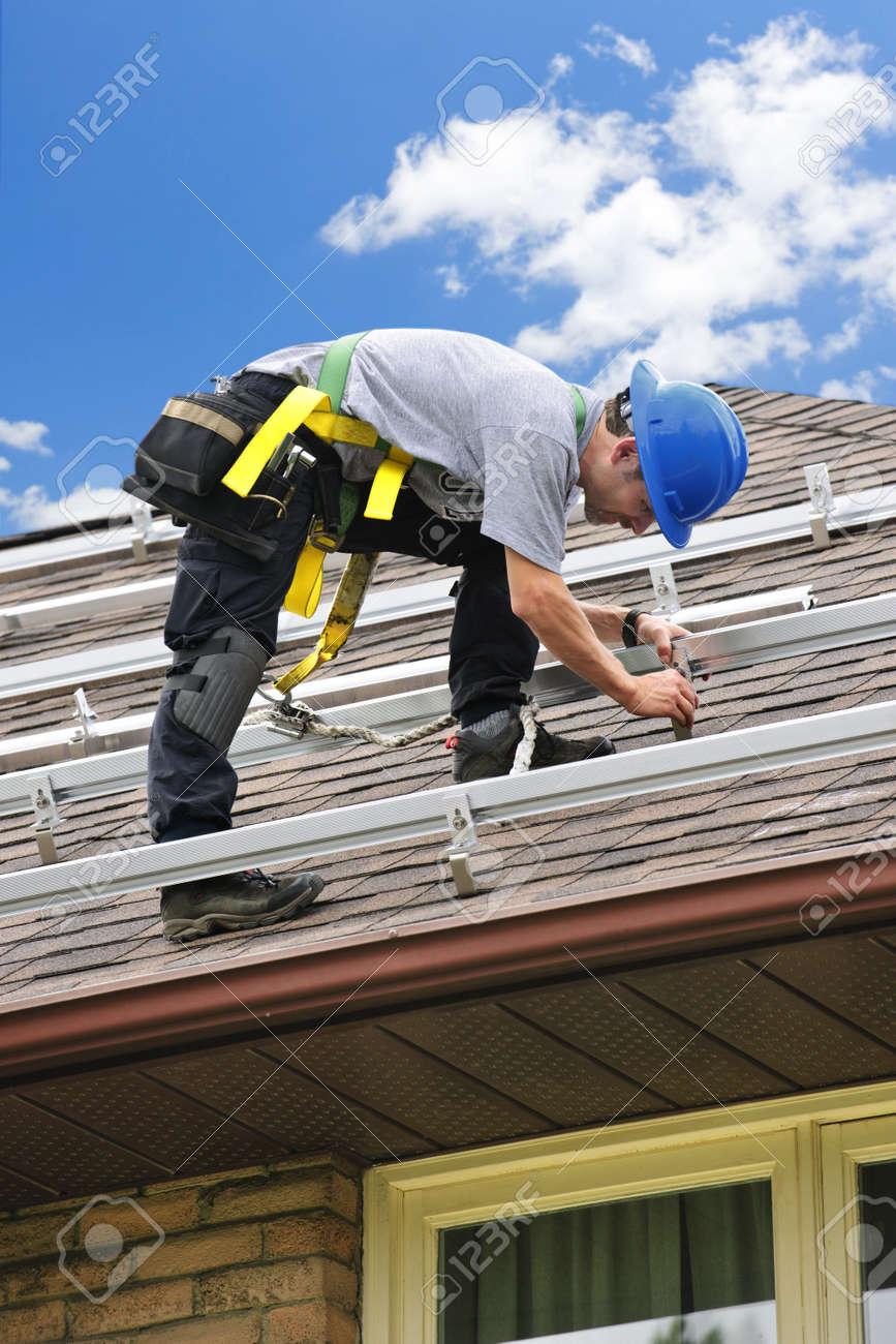 Man installing rails for solar panels on residential house roof Stock Photo - 7881460