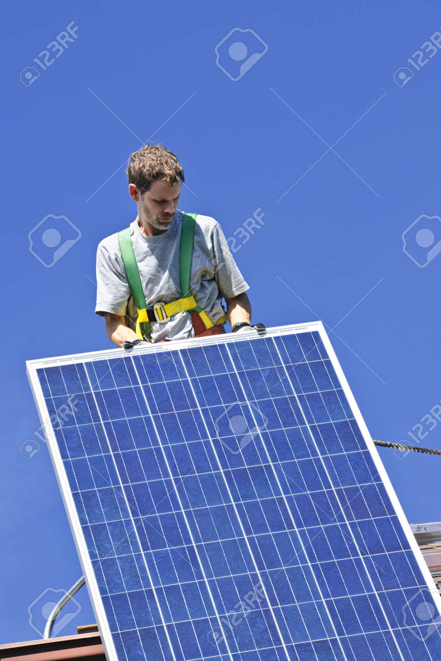 Man installing alternative energy photovoltaic solar panels on roof Stock Photo - 7983268