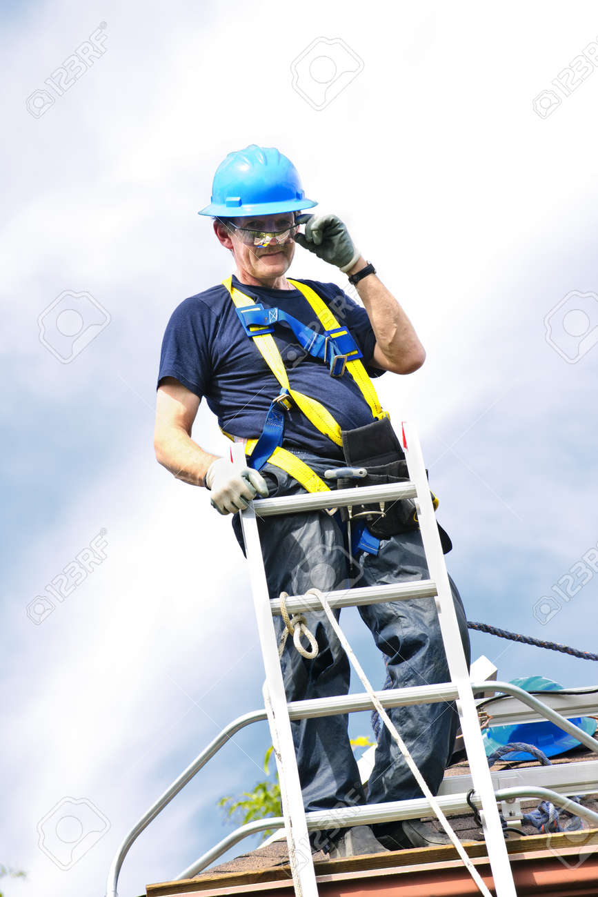 Construction worker standing on roof near ladder Stock Photo - 7983242