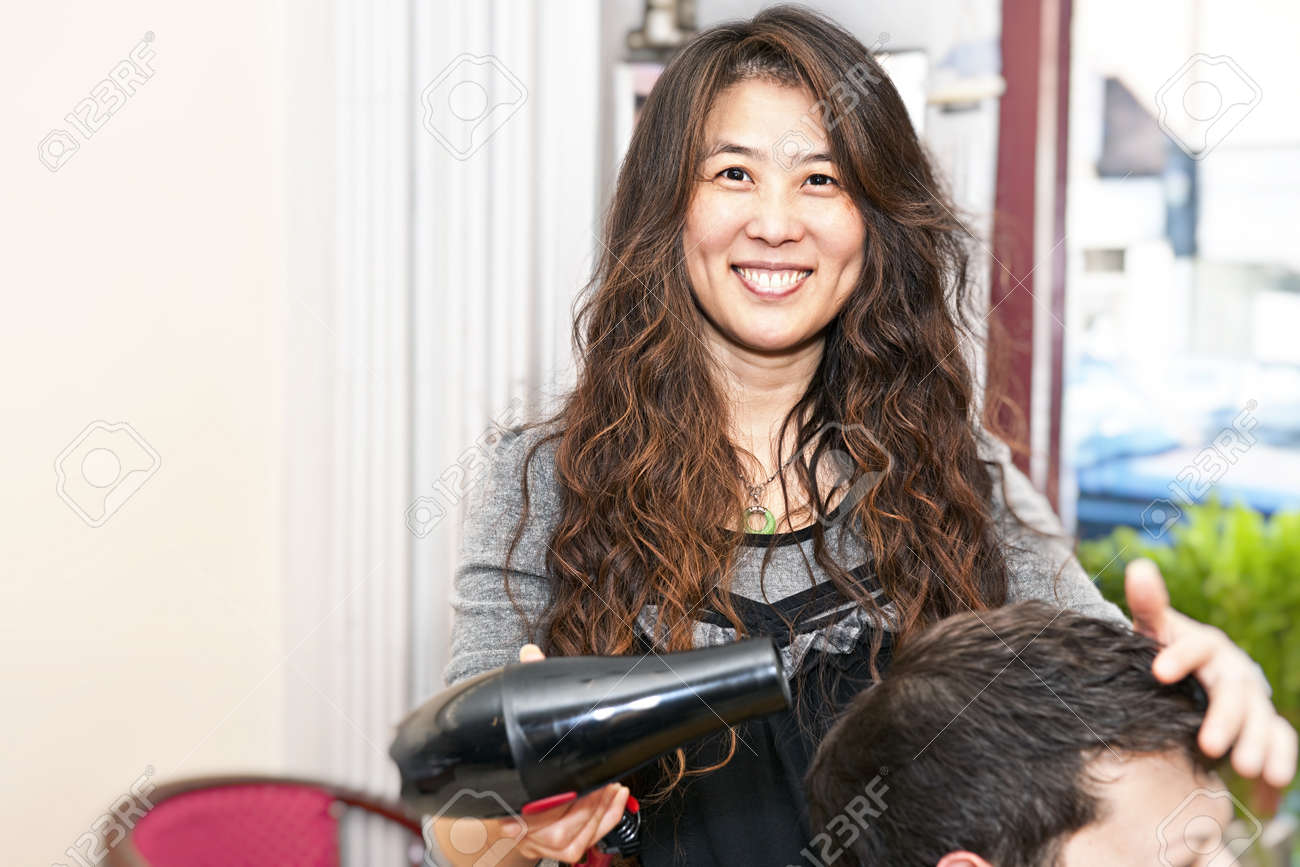 Smiling hairstylist drying hair with hairdryer in her salon Stock Photo - 8338252