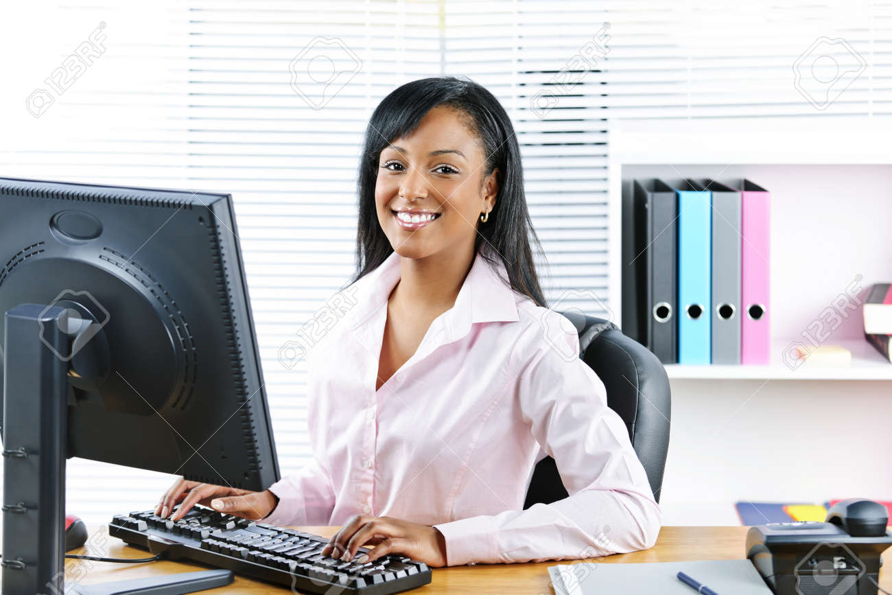 Portrait of happy black business woman at desk typing on computer Stock Photo - 8436686