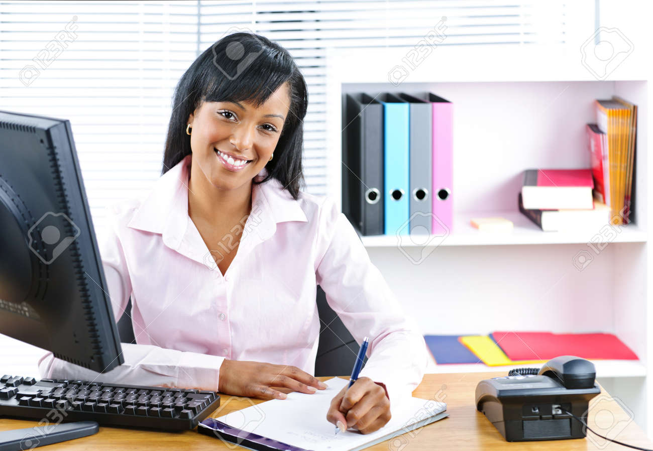 Smiling young black business woman writing at desk in office Stock Photo - 9240570