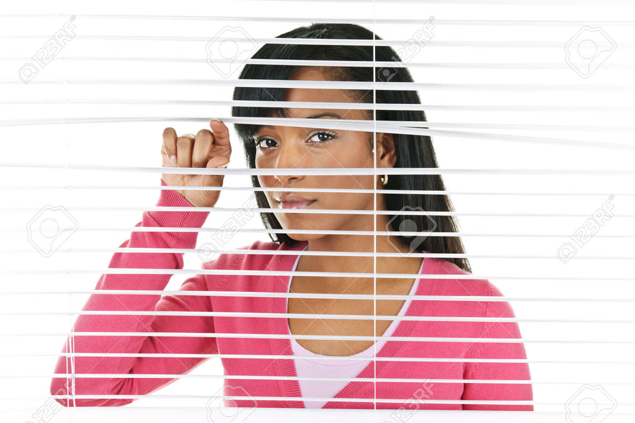 Young black woman looking through horizontal venetian blinds Stock Photo - 9240592