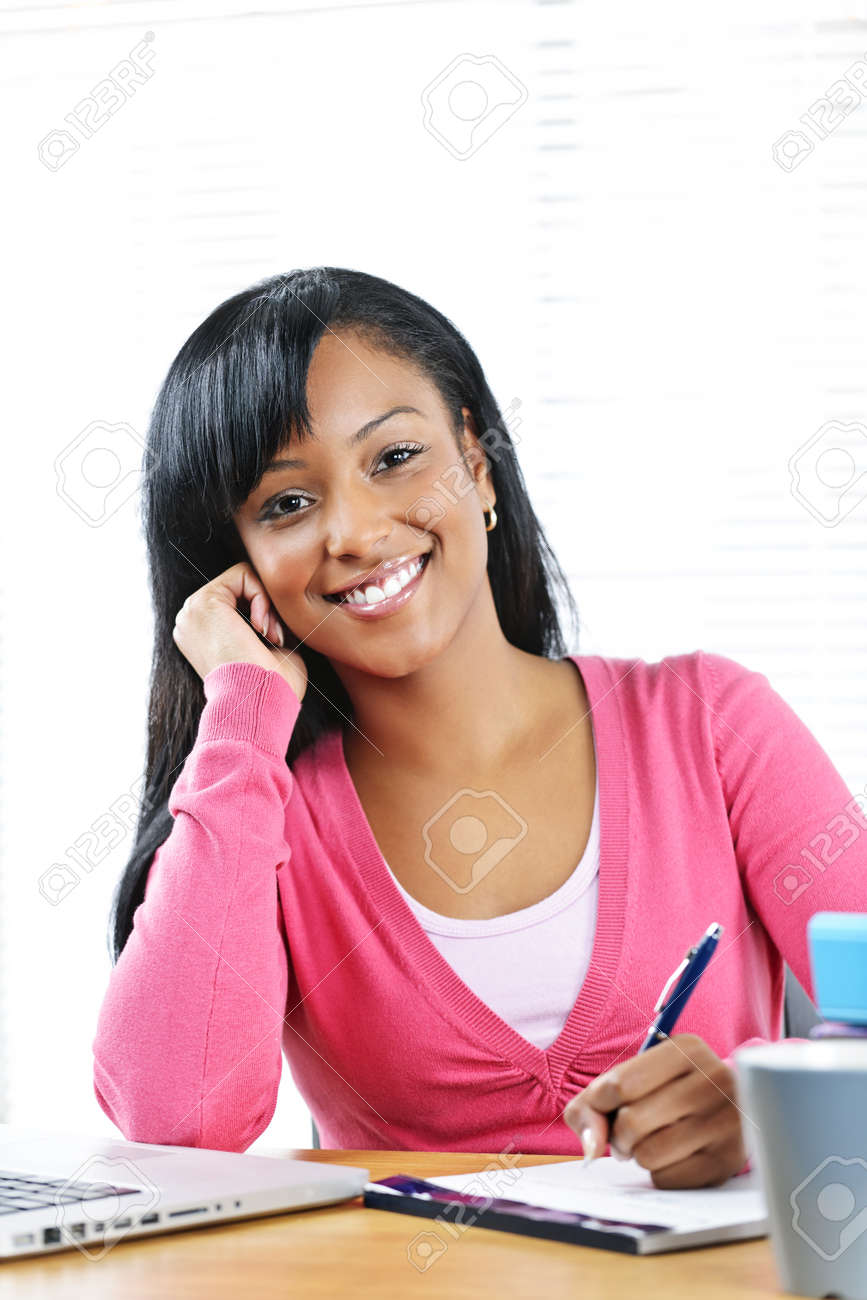 Portrait of smiling young black female student studying at desk Stock Photo - 9379221