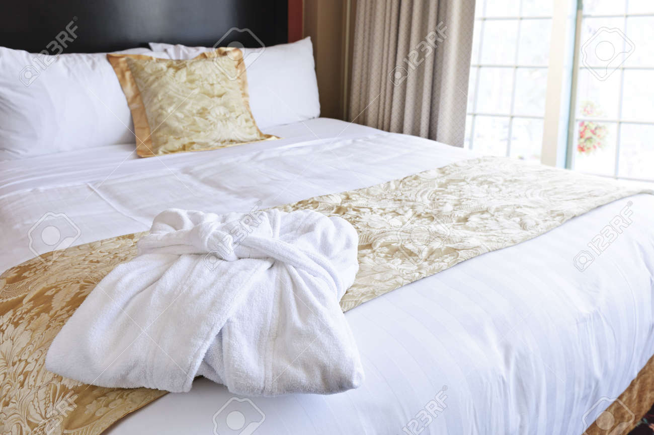 Comfortable bed with clean bathrobe in upscale hotel Stock Photo - 9417858