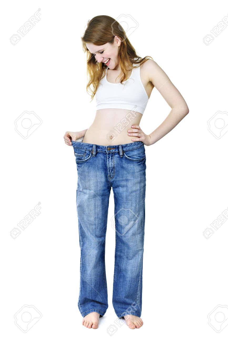 Foto de archivo - Sonriendo encaja joven en jeans antiguos sueltos después  de perder peso aislado en blanco c1ed4ee9bd0