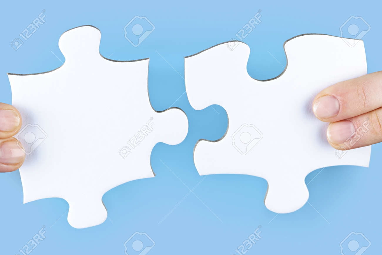 Fingers joining large white blank jigsaw puzzle pieces Stock Photo - 9431946