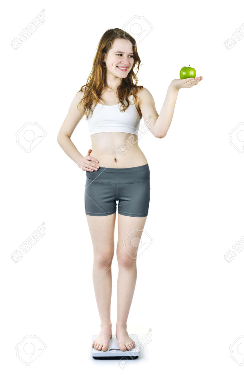 Healthy happy young woman holding green apple standing on bathroom scale Stock Photo - 9434383