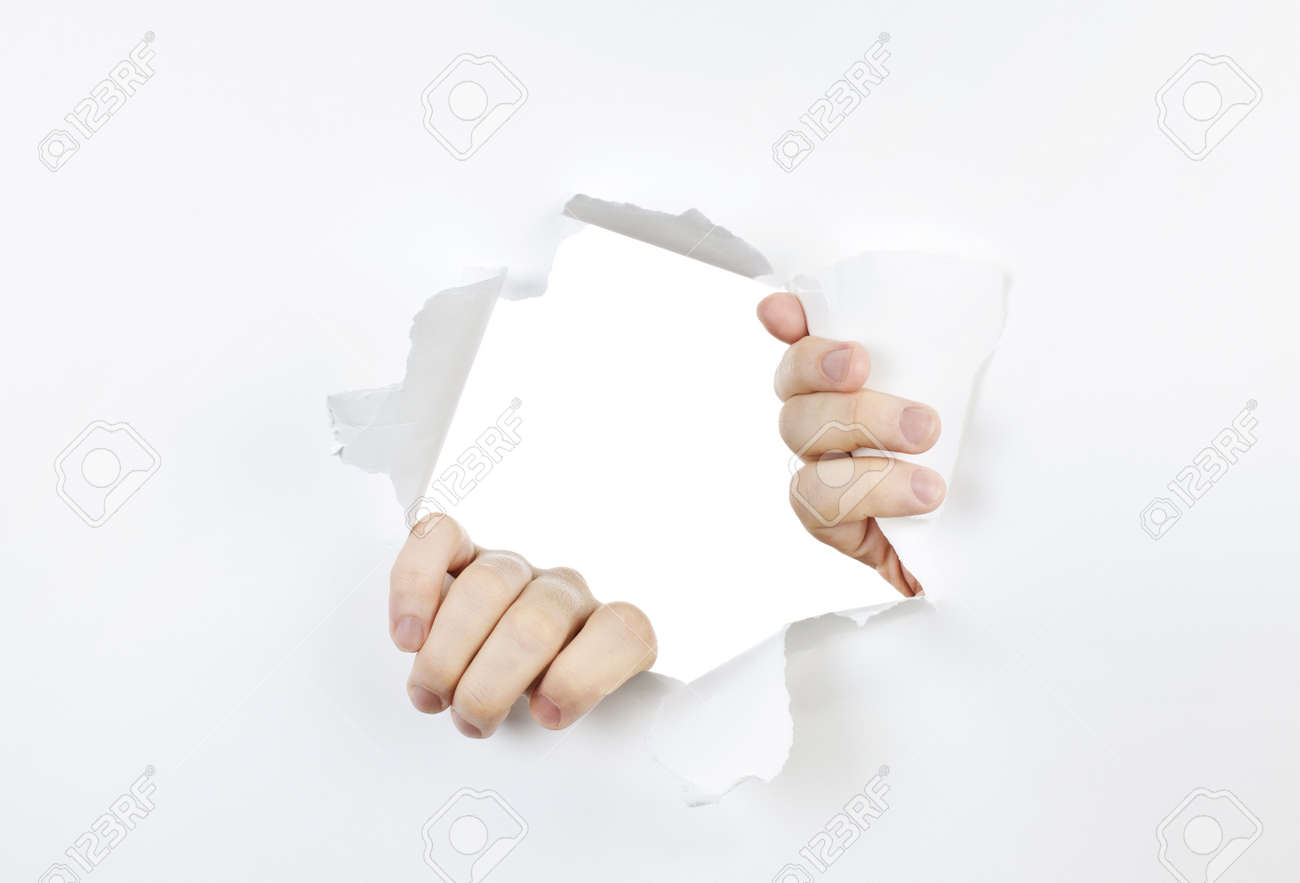 Hands ripping a hole in white paper with torn edges Stock Photo - 9865721