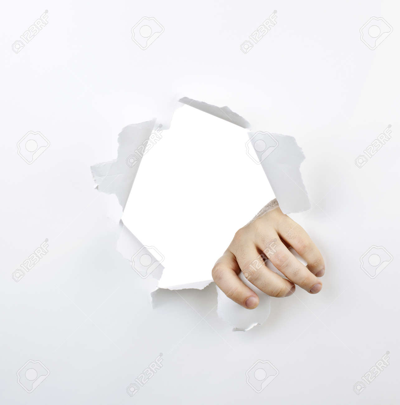 Hand ripping a hole with torn edges in white paper Stock Photo - 9865717