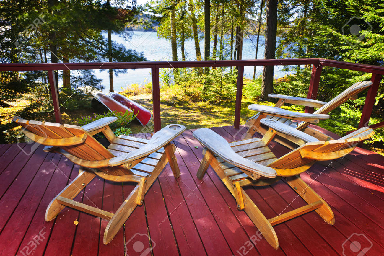 Wooden Deck Of Cottage With Adirondack Chairs At Lake Stock Photo   10500896