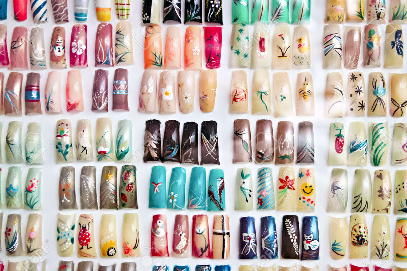Artificial Acrylic Nails Painted In Various Designs On Display ...