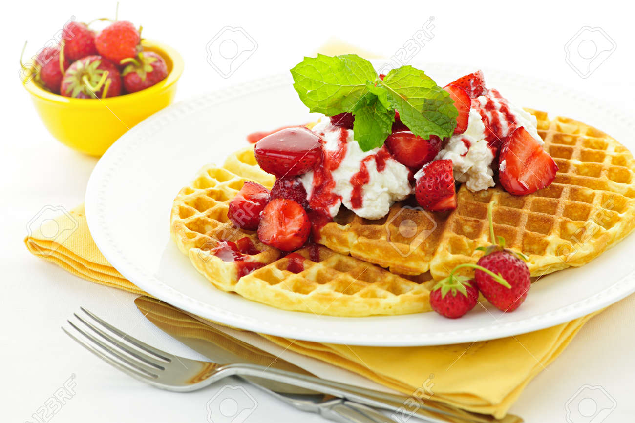 Plate of belgian waffles with fresh strawberries and whipped cream Stock Photo - 10637544