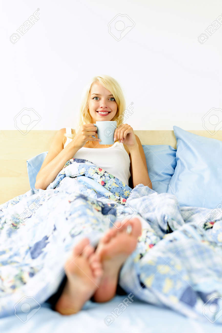 Happy blonde woman drinking coffee and relaxing in bed in the morning Stock Photo - 10708456