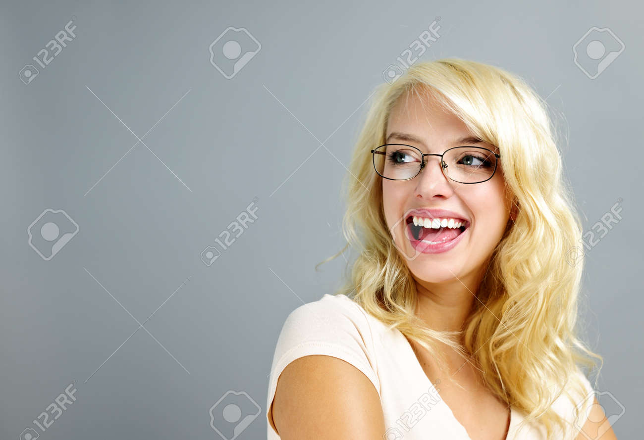 Happy young woman wearing eyeglasses looking to the side on grey background Stock Photo - 11106479