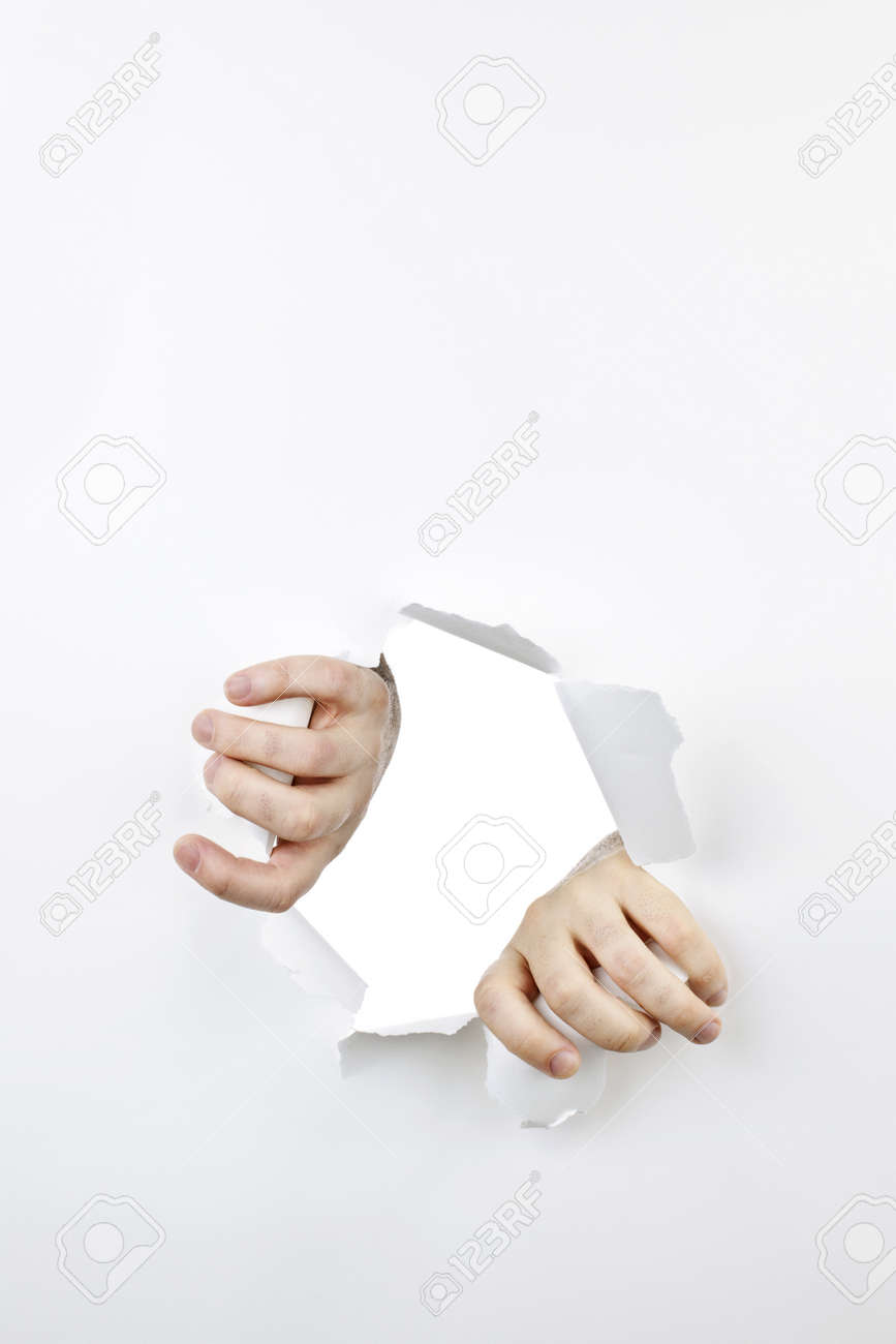 Hands ripping a hole in white paper with torn edges Stock Photo - 11106476