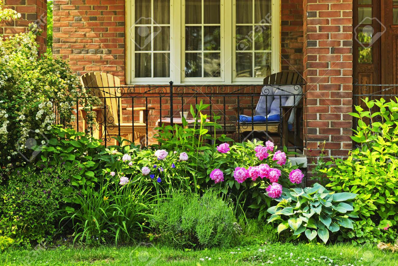 devant la maison avec des chaises et un jardin de fleurs banque d