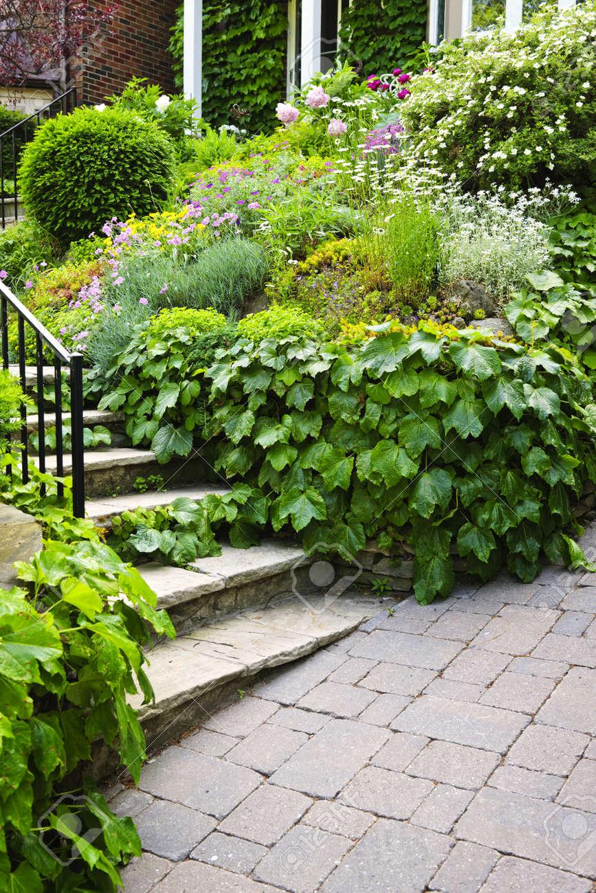 Allée de jardin paysagé avec escalier en pierre naturelle et rampe  métallique