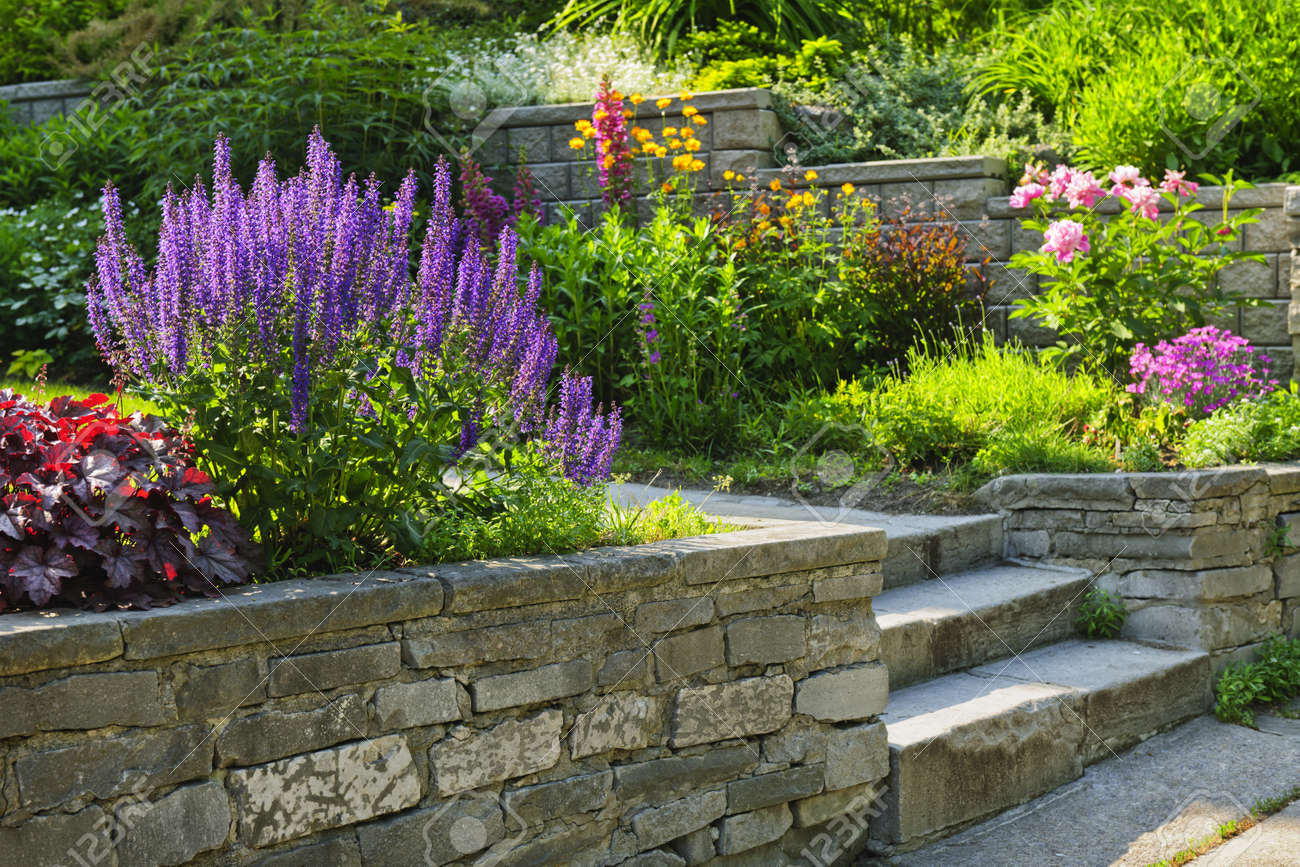 Landscaping flower beds - Natural Stone Landscaping In Home Garden With Steps And Flowerbeds Stock Photo 11930067
