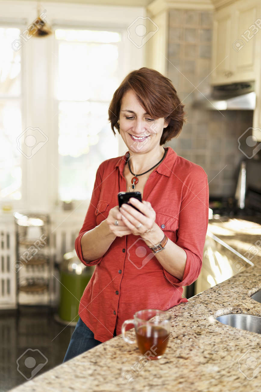 Smiling mature woman texting on phone in kitchen at home Stock Photo - 12389846