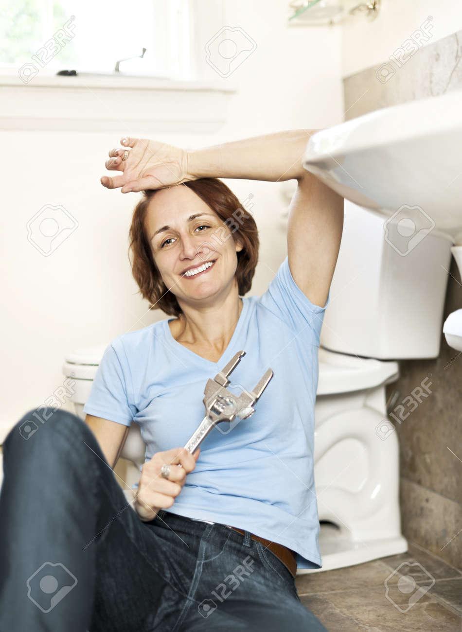 Woman repairing sink in bathroom at home Stock Photo - 12389841