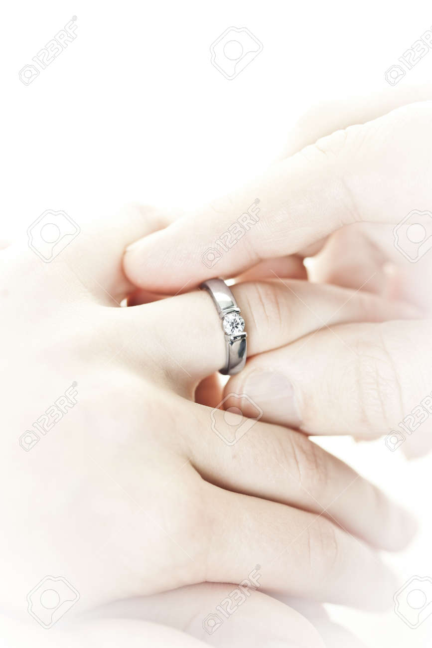 Closeup of hands placing engagement ring on finger Stock Photo - 12922811