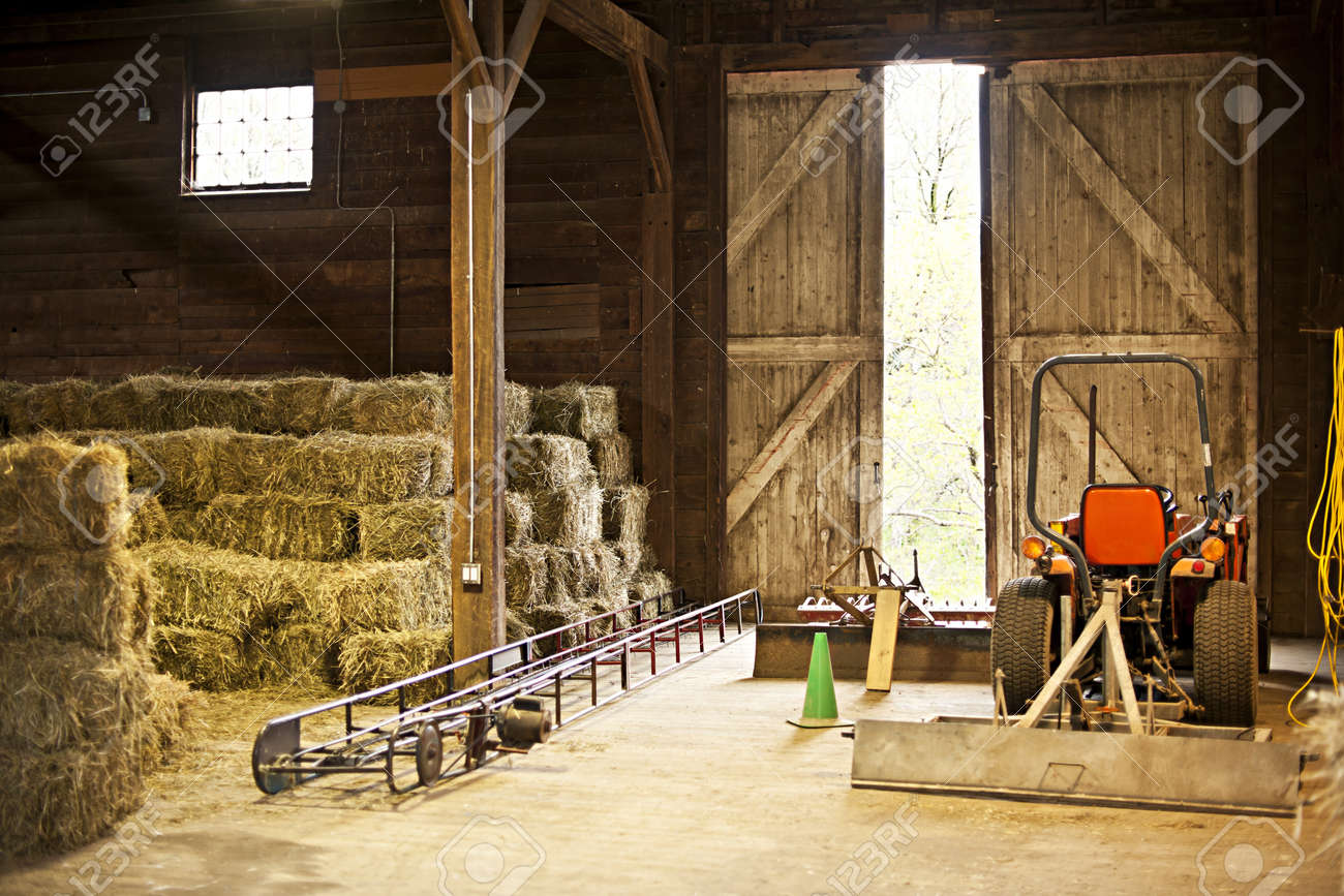 Interior Of Wooden Barn With Hay Bales Stacks And Farm Equipment Stock Photo