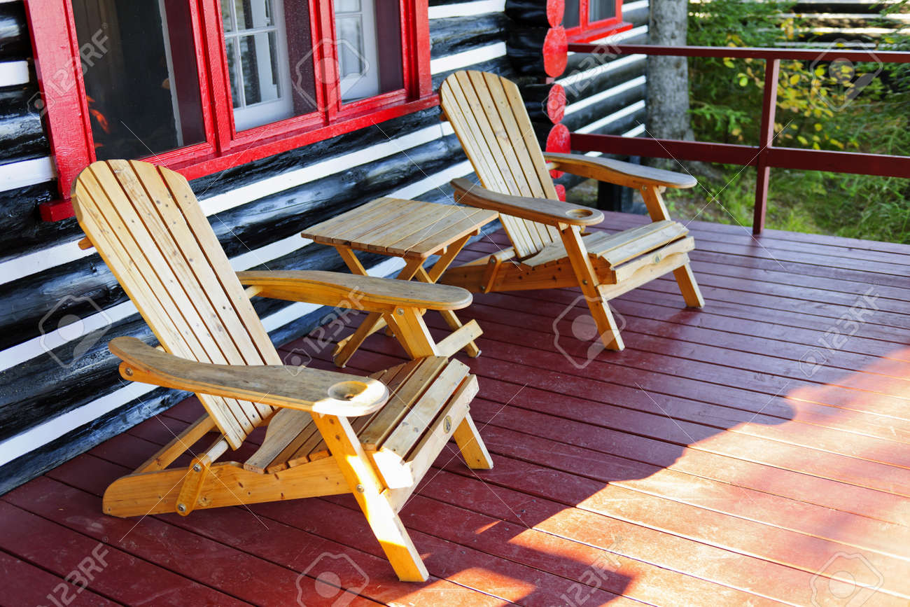 Stock Photo   Wooden Log Cabin Cottage Porch With Adirondack Chairs