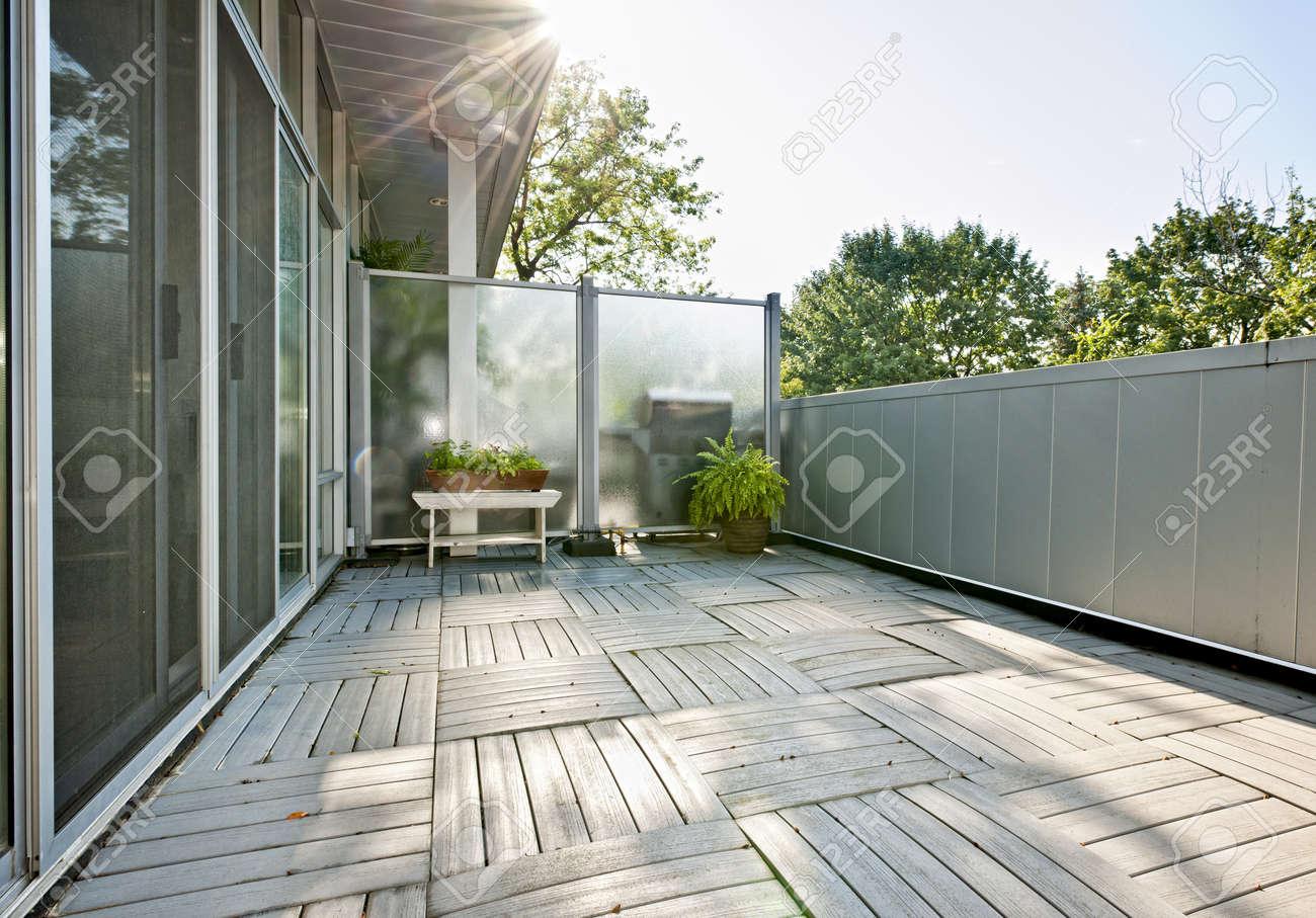 Ampio balcone di condominio moderno, con le piante sulla giornata ...