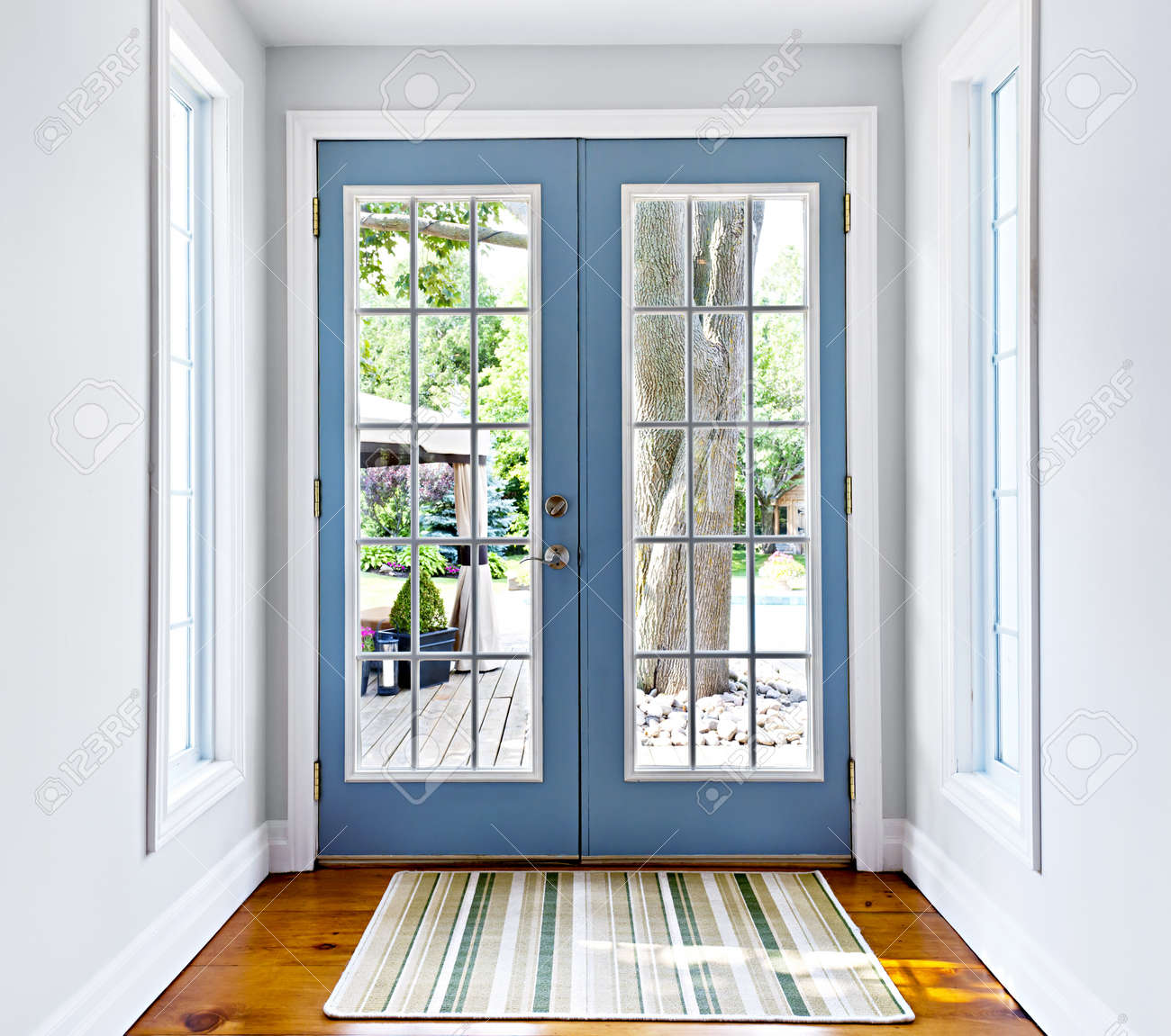 Double Patio French Doors With Windows Exiting To Sunny Backyard Stock Photo