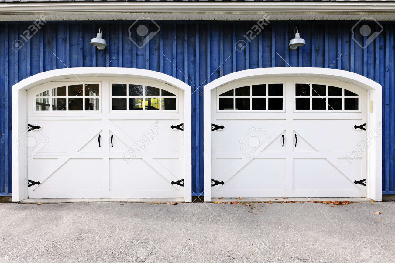 Two white garage doors with windows on blue house Stock Photo - 16524173