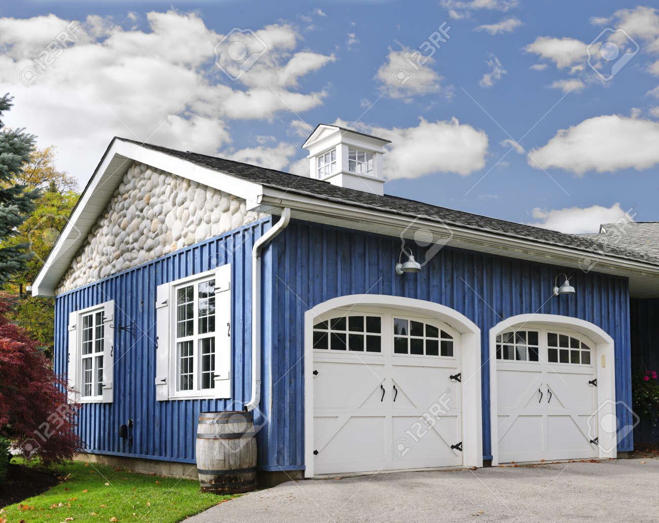 Double car garage with white doors and blue exterior Stock Photo - 16524169
