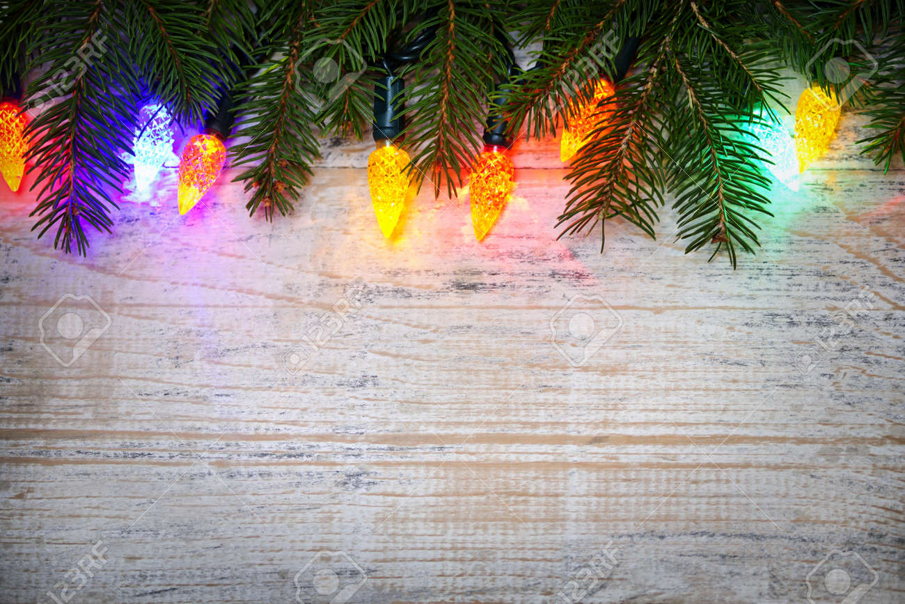 Multicolored Christmas Lights On Spruce Branch With Wooden Background Stock Photo