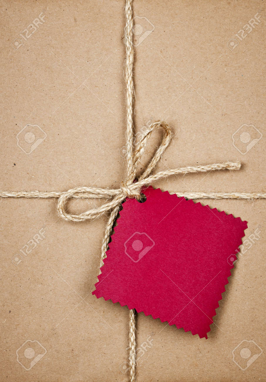 Gift package and red card in brown paper wrapper tied with string close up Stock Photo - 16784836