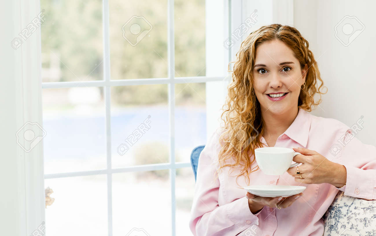 Smiling caucasian woman relaxing by window holding cup of coffee Stock Photo - 17592206