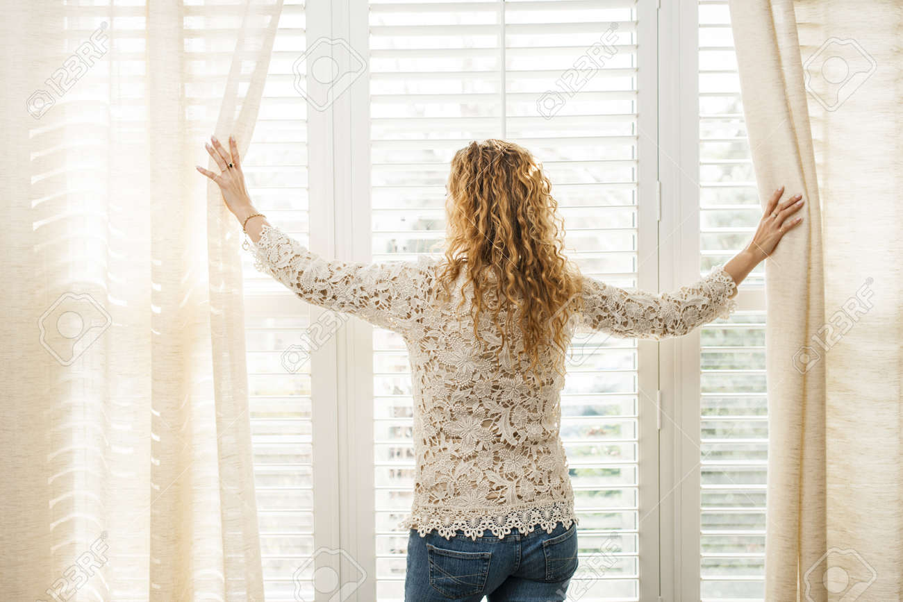 Woman looking out big bright window with curtains and blinds Stock Photo - 17592196