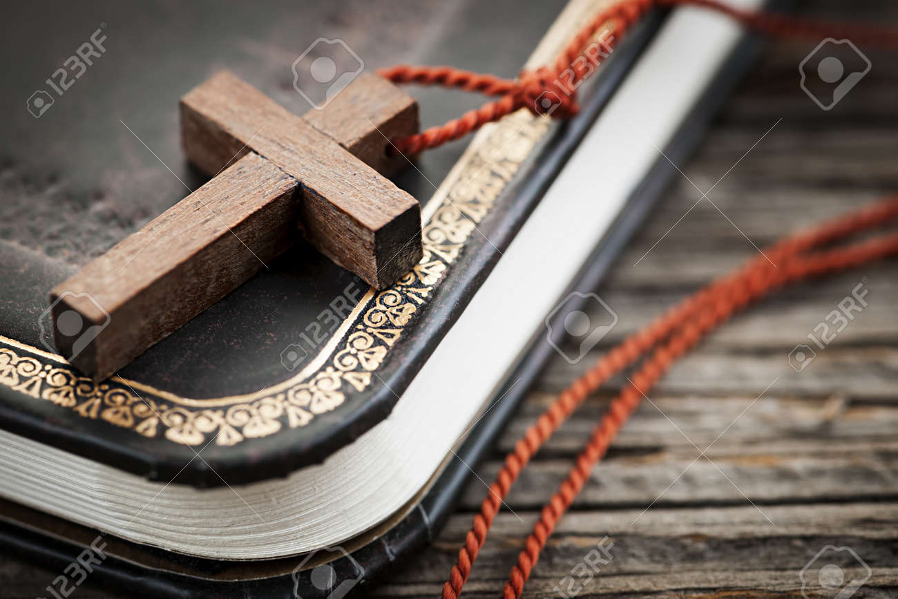 Closeup of simple wooden Christian cross necklace on holy Bible Stock Photo - 18654233