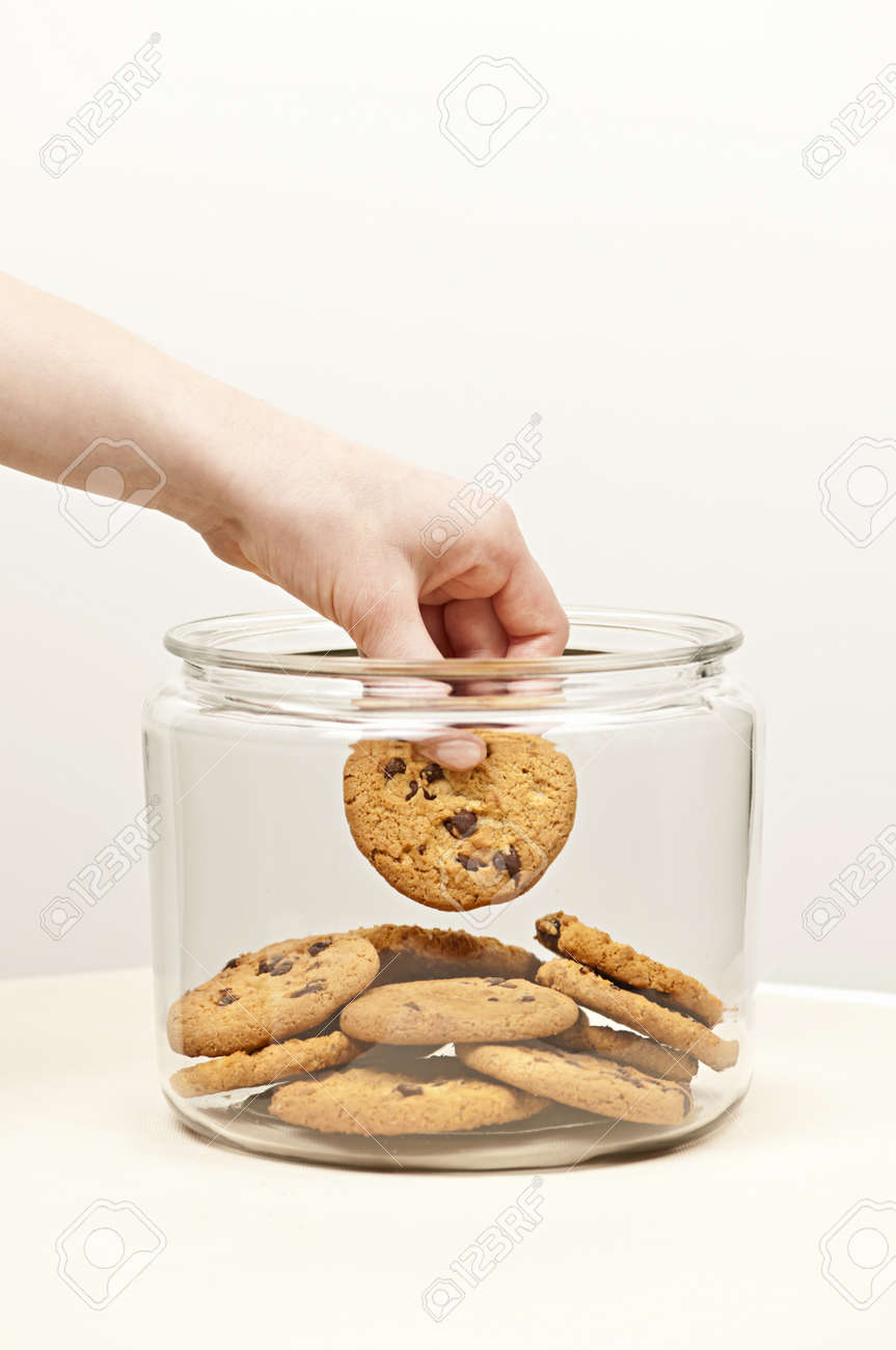 Hand taking chocolate chip cookie from glass jar Stock Photo - 19341206