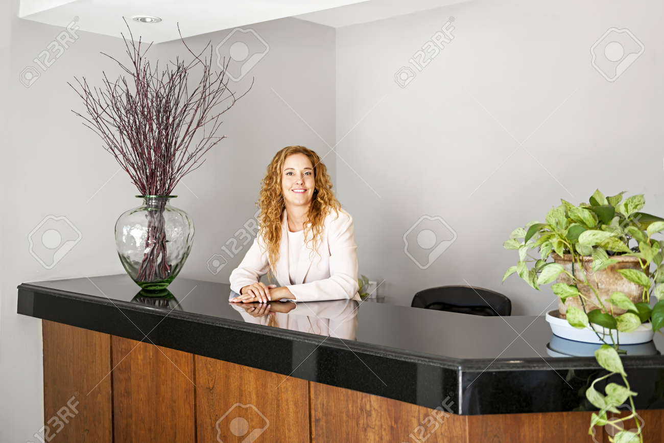 Réceptionniste debout au comptoir daccueil de bureau banque d
